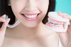 A woman holding braces and Invisalign in different hands